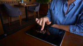 Sluit omhoog vrouwelijke vingers wat betreft het tabletscherm in langzame motie bij koffie stock videobeelden
