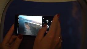 Sluit omhoog vrouwenhand houdend mobiele telefoon en neem een foto buiten vliegtuigvenster stock footage