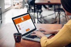 Sluit omhoog vrouwenzitting en online winkelend op laptop computer voeg binnen aan de webpagina van de karfunctie bij koffiewinke Stock Foto