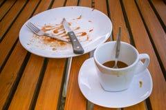 Sluit omhoog vuile koffiekop en lepel het plaatsen op witte schotel, mes en vork op witte vuile schotel Zij zijn op houten lijst stock foto's