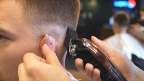Sluit omhoog wapens van kapper die tot mannelijk kapsel maken aan klant met clipper in salon Handen van herenkapper scherp haar v stock footage