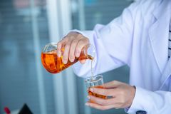 Sluit omhoog wetenschapperhand die oranje vloeistof gieten stock fotografie