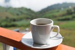 Sluit omhoog witte kop van hete koffie op balkonrand met openluchtna Royalty-vrije Stock Fotografie