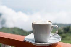 Sluit omhoog witte kop van hete koffie op balkonrand met openluchtna Stock Foto's