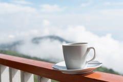 Sluit omhoog witte kop van hete koffie op balkonrand met openluchtna Royalty-vrije Stock Foto