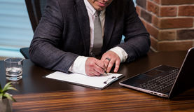 Sluit omhoog zakenman die documenten ondertekenen De zakenman ondertekent a stock foto