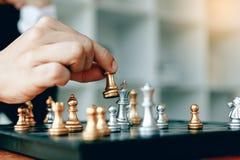 Sluit omhoog zakenmanhand die de koning in een schaakspel bewegen voor winst royalty-vrije stock fotografie