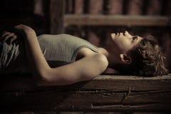 Sluit omhoog zijaanzicht van jongen het leggen op houten bank Royalty-vrije Stock Foto's