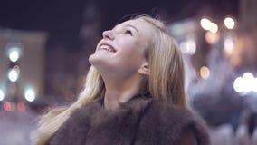 Sluit omhoog zijaanzicht van tevreden vrolijk modieus aantrekkelijk mooi jong gelukkig meisje die in bontjas de hemel bekijken stock video