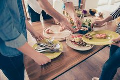 Sluit opgedoken foto van mensen die de lijst met achterdeks voedsel opruimen stock afbeeldingen