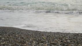 Sluit overzeese omhoog golven en kust met overzeese kiezelstenen stock videobeelden