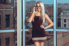 Sluit portret het glimlachen omhoog de sprekende telefoon van de blondevrouw dichtbij La royalty-vrije stock fotografie