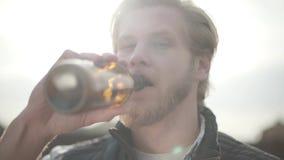 Sluit portret omhoog knap gebaard mens het drinken bier en in openlucht het genieten van van drank De kerel proeft lagerbier van  stock videobeelden