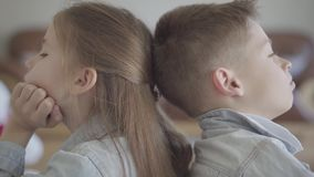 Sluit portret omhoog tweelingjongen en het meisje zit op de vloer van woonkamer rijtjes boos aan elkaar Broer en zuster stock video