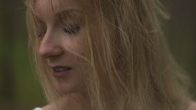 Sluit portret omhoog zijaanzicht - de Mooie jonge bosnimf van de blondevrouw in witte kleding in altijdgroen hout stock video
