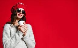 Sluit portret van een glimlachend jong meisje in hoedenholding weghalen omhoog koffiekop royalty-vrije stock afbeeldingen