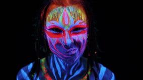 Sluit portret van jong aanbiddelijk lichaam arted omhoog meisje in ultraviolet licht op zwarte achtergrond Zwarte lichte gloeiend stock video