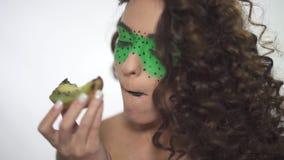 Sluit portret van jong mooi krullend meisje met creatief maken omhoog omhoog het eten van kiwi stock footage