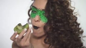Sluit portret van jong mooi krullend meisje met creatief maken omhoog omhoog het eten van sappige kiwi stock footage