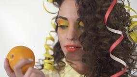 Sluit portret van jong speels glimlachend meisje met helder maken omhoog omhoog het houden oranje Langzame Motie stock footage