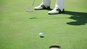 Sluit rechtstreeks omhoog geschoten op een golfspeler wanneer klappen witte golfbal aan de zaal stock footage