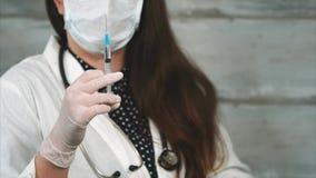 Sluit schot op een vrouwelijke artsen` s hand, die een spuit met geneeskunde controleert stock videobeelden