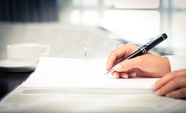 Sluit schot van een menselijke hand schrijvend iets op het document Royalty-vrije Stock Afbeelding