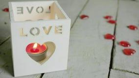 Sluit schot van rode kaars in lantaarn met liefdetekst op het Rood nam toe stock videobeelden
