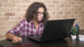 sluit tienerjongen met krullend donkerbruin haar, in het werk van het plaidoverhemd aangaande een grafiektablet die een naald geb stock footage