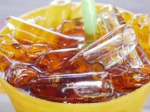 Sluit tot gele plastic kop van kola of vercooks met ijs, selecti Stock Fotografie