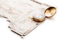 Sluit tot gouden zeevaartkompas op oude uitstekende kaart met vals eiland van Piratenschat Stock Afbeelding
