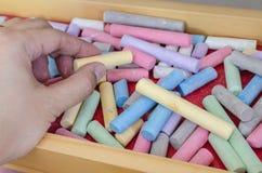 Sluit tot het krijt van de handholding met multicoloured krijt Stock Afbeelding