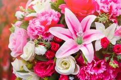 Sluit tot kleurrijk plastic roze lilly bloeit met rozen en l Stock Foto's