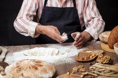 Sluit van bakker overhandigt het kneden omhoog deeg en het maken van brood met een deegrol stock foto