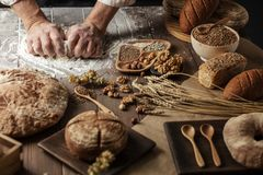 Sluit van bakker overhandigt het kneden omhoog deeg en het maken van brood met een deegrol stock afbeelding
