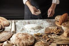Sluit van bakker overhandigt het kneden omhoog deeg en het maken van brood met een deegrol stock afbeeldingen