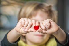 Sluit van boy's overhandigt omhoog het houden van een rood hart Stock Fotografie