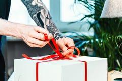 Sluit van de banden van de mensenkok omhoog rood lint bij de witte cake verpakking royalty-vrije stock afbeeldingen