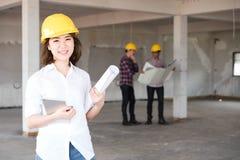 Sluit van de de ingenieursslijtage van de vrouwenbouw omhoog gele de veiligheidshelm w Stock Foto