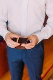 Sluit van de jonge mens binnen tegenhoudt riem in zijn handen die modieuze gesp tonen Royalty-vrije Stock Foto