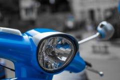 Sluit van de koplamp van een blauwe klassieke autoped met defocused omhoog achtergrond stock foto