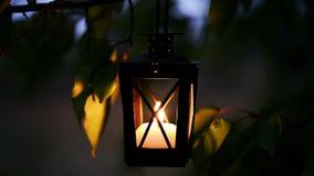 Sluit van de lichten van de vrouwenhand omhoog een kaars in de lantaarn van de metallkaars stock videobeelden