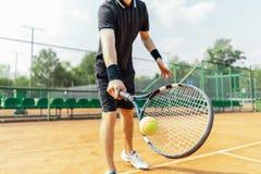 Sluit van de racket van de mensenholding bij rechts en afstraffing omhoog een tennisbal stock afbeeldingen