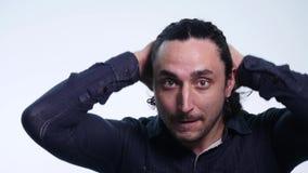 Sluit van een aantrekkelijke jonge mens met krullende haardraaien omhoog haar hoofd onderzoekend de camera op witte achtergrond stock videobeelden