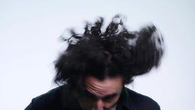 Sluit van een aantrekkelijke jonge mens met krullende haardraaien omhoog haar hoofd onderzoekend de camera op witte achtergrond stock video