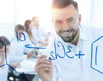 Sluit van een glimlachende wetenschapper uitwerkt een formule op blackboa Stock Afbeeldingen