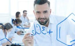 Sluit van een glimlachende wetenschapper uitwerkt een formule op het bord Stock Afbeelding