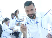Sluit van een glimlachende wetenschapper uitwerkt een formule op het bord Stock Foto