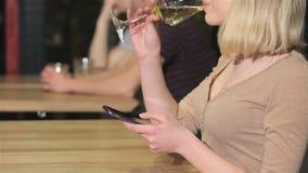 Sluit van een jonge vrouw drinkt omhoog de telefoon van de wijnholding in haar hand stock videobeelden