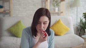Sluit van een jonge vrouw smeert omhoog doen barsten lippen helend balsemzitting stock video